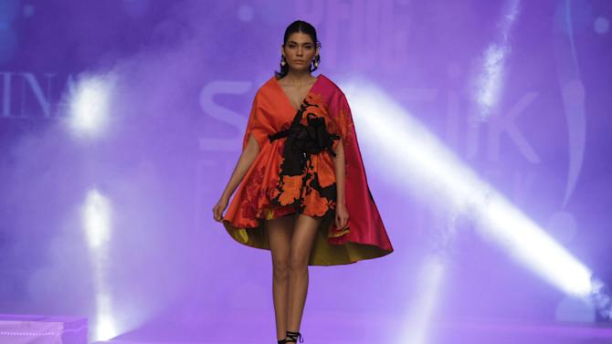 FILE - In this Tuesday, April 21, 2015 file photo, a model presents creations by Pakistani designer Sana Safinaz on the last day of PFDC Sunsilk Fashion Week Spring/Summer 2015 in Lahore, Pakistan. (AP Photo/K.M. Chaudary, File)
