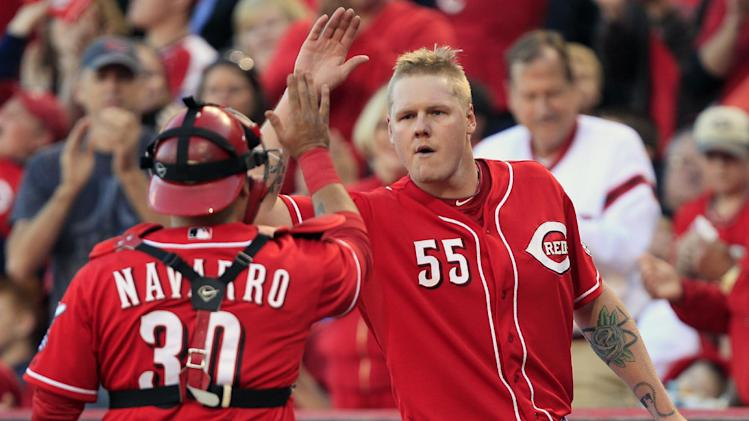 Cincinnati Reds starting pitcher Mat Latos (55) high-fives catcher Dioner Navarro at the end of the eighth inning of a baseball game against the Los Angeles Dodgers, Saturday, Sept. 22, 2012, in Cincinnati. Cincinnati won 6-0 to clinch the National League Central Division. (AP Photo/Al Behrman)