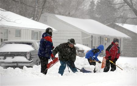 A family digs snow out of their driveway during a blizzard in Overland Park, Kansas, February 21, 2013. REUTERS/Dave Kaup