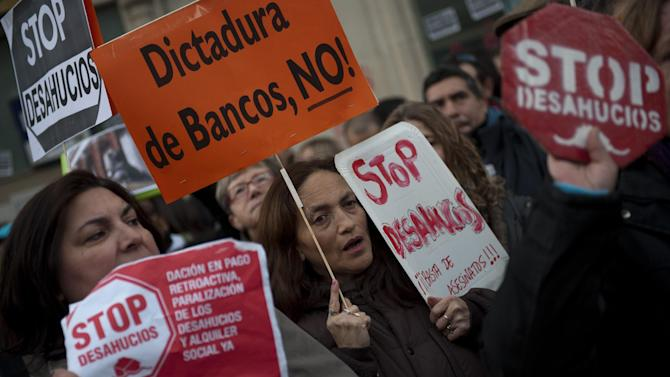 Demonstrators, some of them from the Platform of People Affected by Mortgages, a group campaigning to stop evictions, holding banners reading 'No to banks dictatorship' and 'Stop Evictions' shout slogans against the government outside the Parliament as the Spanish Parliament considers whether to admit a popular petition to change mortgage laws and halt evictions of those unable to pay mortgages to a vote in Madrid, Tuesday, Feb. 12, 2013. The government agreed to consider changes to the law on mortgages after pressure from opposition parties and a growing public outcry, including a petition that was signed by 1.4 million people – enough signatures to force Parliament to discuss alterations to the law in a special session. (AP Photo/Daniel Ochoa de Olza)
