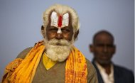 "An Indian Hindu Sadhu (left) and a newly initiated Sadhu look on near their tent at the Kumbh Mela in Allahabad on February 19, 2013. Authorities at the festival on Sunday said the last batch of holy men marked the end of the Kumbh by plunging into the river Ganges and other pilgrims filled the ""Ganga Jal"" (holy water) in plastic bottles for religious ceremonies at home"