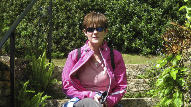 Vicki Gilbert sits on stone steps in Wiltshire, England in this undated photo made available by the family on Tuesday, March 26, 2013. In 2010, Gilbert was diagnosed with breast cancer and then found she carries the mutated BRCA1 gene which may make her pre-disposed to ovarian cancer. Gilbert decided to have ovaries removed to prevent the potential onset of further cancer, and her breast cancer is in remission. A huge international effort involving more than 100 institutions and genetic tests on 200,000 people has uncovered dozens of signposts in DNA that can help reveal further a person's risk for breast, ovarian or prostate cancer, scientists reported Wednesday, March 27, 2013. It's the latest mega-collaboration to learn more about the intricate mechanisms that lead to cancer. (AP Photo)