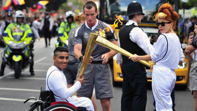 In this Saturday, July 21, 2012,  photo provided by LOCOG, singer Paloma Faith passes the Olympic Flame to torchbearer  Sheikh Sheikh on the Torch Relay leg through London. The opening ceremonies of the Olympic Games are scheduled for Friday, July 27. (AP Photo/LOCOG, Ben Birchall)
