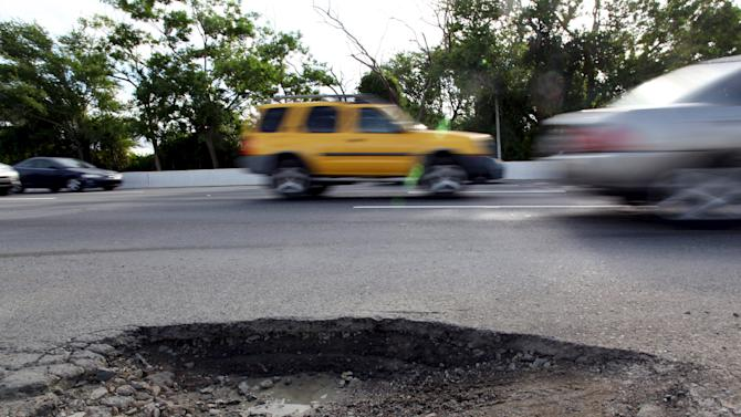 Cars drive past a pothole on a highway that connects the metropolitan area with the east side of the island, in Fajardo, on the outskirts of San Juan