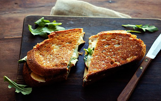 Photo by: FoodessApple-Cheddar Grilled CheeseSliced red onion and peppery arugula add piquancy to this classic fall sandwich.   Recipe: Apple-Cheddar Grilled Cheese