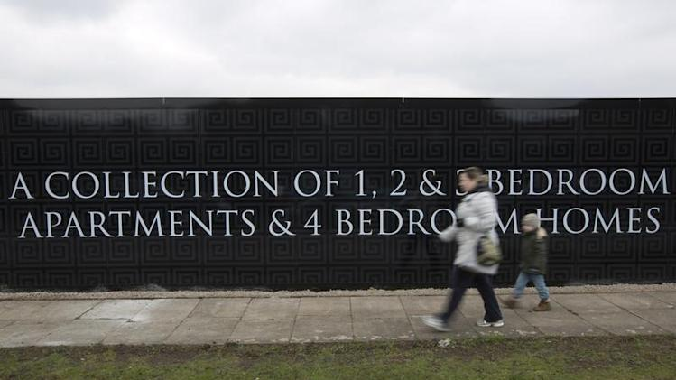 A woman and child walk past an advertisement for new residential property development in London