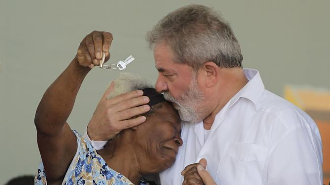 FILE - In this Oct. 25, 2010 file photo, Brazil's President Luiz Inacio Lula da Silva, right, kisses Corina Edelvina Bento as she receives the keys to her new home during the inauguration ceremony of a government-built housing complex at the Complexo do Alemao slum in Rio de Janeiro, Brazil. Silva, 65, who will hand power to his political protege Dilma Rousseff on Jan. 1, 2011, leaves a nation transformed from a perennial underachiever into one with economic and political clout, model social programs and a swagger as it prepares to host the 2014 World Cup and the 2016 Olympics.  (AP Photo/Felipe Dana, file)