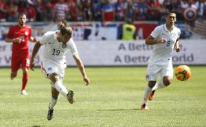 Graham Zusi of the U.S. takes a shot as his teammate Clint Dempsey looks on during their international friendly soccer match against Turkey in Harrison