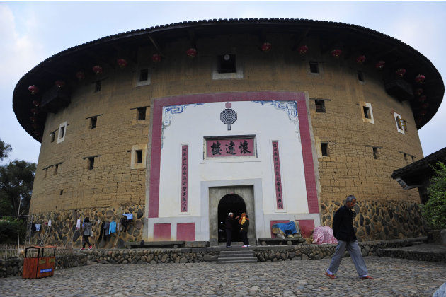 Man walks past Huaiyuan Lou, one of the best protected Fujian Tulou built in the year 1909, in Nanjing county