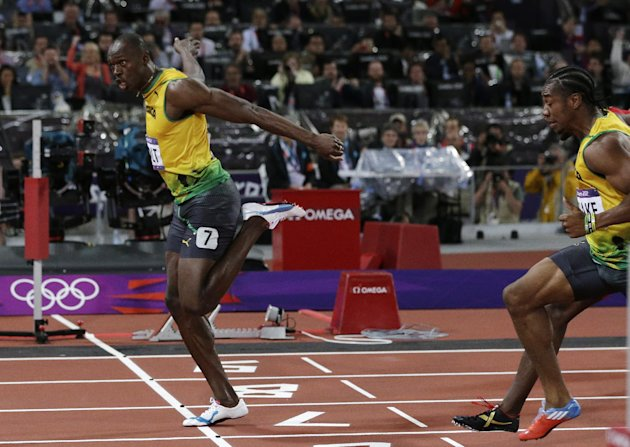 Jamaica's Usain Bolt, left, crosses the finish line ahead of Jamaica's Yohan Blake to win gold in the men's 100-meter final during the athletics in the Olympic Stadium at the 2012 Summer Olympics, London, Sunday, Aug. 5, 2012. (AP Photo/David J. Phillip )