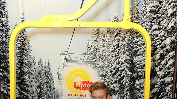 IMAGE DISTRIBUTED FOR LIPTON: One for the bucket list,actor Duncan Penn of MTV's Buried Life rides an indoor ski lift with a hot cup of tea at the Lipton Uplift Lounge during Sundance on Saturday Jan. 19, 2013, in Park City, UT. (Photo by Jordan Strauss/Invision for Lipton/AP Images)