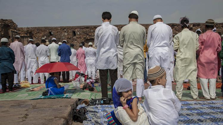 Indian Muslim children sit as elders offer prayers on Eid al-Fitr at the Feroz Shah Kotla Mosque in New Delhi, India, Tuesday, July 29, 2014. Millions of Muslims across the world are celebrating the Eid al-Fitr holiday, which marks the end of the month-long fast of Ramadan. (AP Photo/Tsering Topgyal)