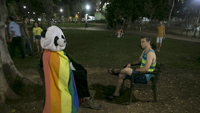A man dressed in a panda costume sits during a protest against the violence towards the gay community in Tel Aviv