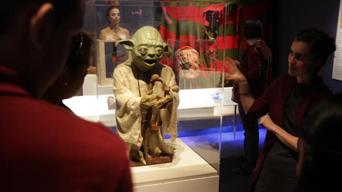 """This undated image provided by the Museum of the Moving Image  shows young visitors encountering Yoda, the """"Star Wars"""" character, in the museum's core exhibition """"Behind the Screen,"""" in Astoria section of the Queens borough of New York. The artifact, which was a gift to the museum from Stuart Freeborn, is one of a number of items related to popular movies on display at the museum, which also offers hands-on exhibits ranging from old video games to equipment that lets visitors dub their own voices into a scene from a famous film. The Museum of the Moving Image is one of a number of attractions in Astoria and the adjacent neighborhood of Long Island City. Tourists are turning up in Long Island City these days because of a hotel boom there. (AP Photo/Museum of the Moving Image, Brian Palmer)"""