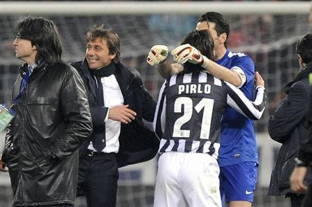 Juventus' Andrea Pirlo (21) celebrates with his coach Antonio Conte (2nd L) and Gianluigi Buffon (R) at the end of their Italian Serie A soccer match against Genoa at Luigi Ferraris stadium in Gen