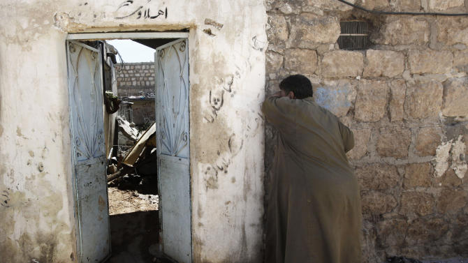 A Syrian man reacts outside of his damaged home, which was destroyed by a Syrian government airstrike earlier in the day, in Marea village, on the outskirts of Aleppo, Syria, Sunday, Sept. 23, 2012. Syria's bloody 18-month conflict, which activists say has killed nearly 30,000 people, has so far eluded all attempts at international mediation. (AP Photo/Hussein Malla)