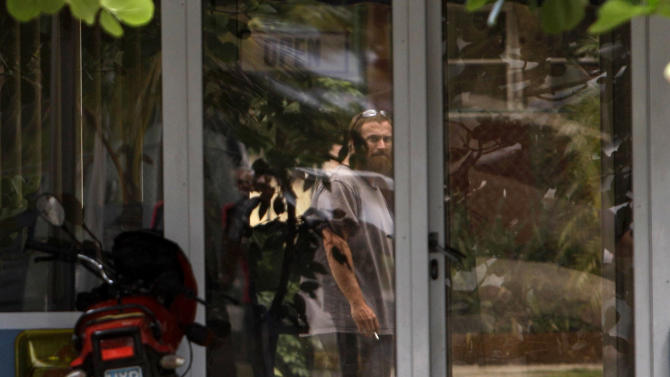 Joshua Michael Hakken stands behind a glass door at the Hemingway Marina in Havana, Cuba, Tuesday, April 9, 2013. Hakken and his wife Sharyn, who had lost custody of their two young boys, allegedly kidnapped them from Sharyn's parents in Florida and fled by boat to Havana. A foreign ministry official told The Associated Press in a written statement Tuesday that Cuba had informed U.S. authorities of the country's decision to turn over Hakken, his wife and their two young boys. She did not say when the handover would occur. (AP Photo/Franklin Reyes)