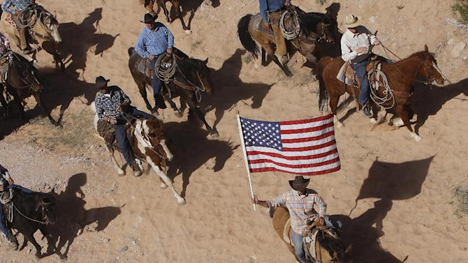 The Bundy family and their supporters fly the American flag as their cattle were released by the Bureau of Land Management back onto public land outside of Bunkerville, Nev. on April 12, 2014. (AP Photo/Las Vegas Review-Journal, Jason Bean)