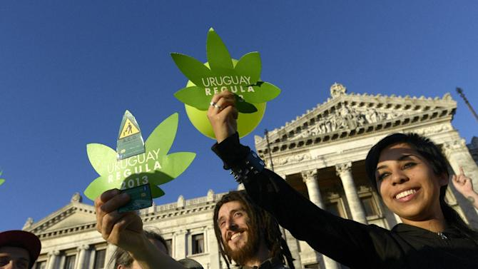 Activists gather in front of Uruguayan Congress as the Senate in support of the legalization of marijuana outside the Congress in Montevideo, Uruguay, Tuesday, Dec. 10, 2013. Uruguay's Senate gave final congressional approval Tuesday to create the world's first national marketplace for legal marijuana, an audacious experiment that will have the government oversee production, sales and consumption of a drug illegal almost everywhere else. (AP Photo/Matilde Campodonico)