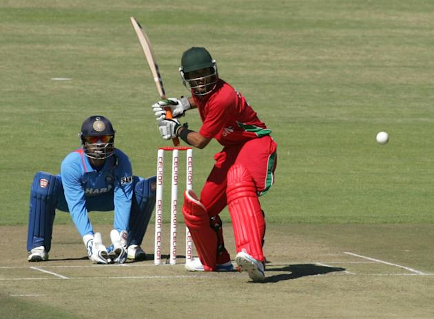 Zimbabwe's batsman Sikanda Raza Butt (R) hits the ball as Indian wicket keeper Dinesh Kathik (L) looks on during the first of the five ODI cricket series matches between India and hosts Zimbabwe at th