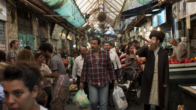 In this Oct. 12, 2012 photo an Ultra-orthodox Jewish man blows a trumpet to announce the starting of the Sabbath, Judaism's biblically-mandated day of rest, at the Mahane Yehuda market in Jerusalem. Though most Israelis are secular, Israel's founding fathers gave Judaism a formal place in the country's affairs and Ultra-Orthodox rabbis strictly govern Jewish practices such as weddings, divorces, and burials. The Ultra-Orthodox are also perennial kingmakers in Israeli coalition politics, though they make up only ten percent of the country's population. (AP Photo/Bernat Armangue)