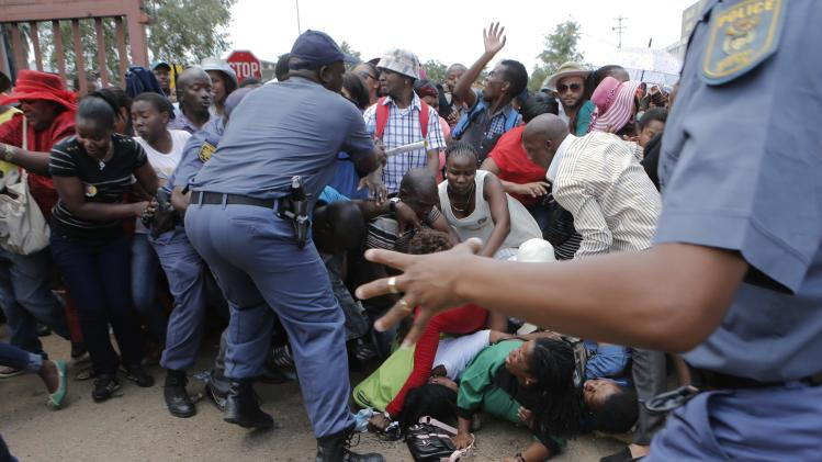 South African police control the crowd following a crush as people jostled to see former South African president Nelson Mandela on the last day of his lying in state in Pretoria, South Africa, Friday, Dec. 13, 2013. (AP Photo/Tsvangirayi Mukwazhi)