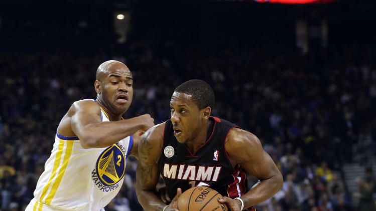 Miami Heat's Mario Chalmers, right, dribbles past Golden State Warriors' Jarrett Jack (2) during the first half of an NBA basketball game in Oakland, Calif., Wednesday, Jan. 16, 2013. (AP Photo/Marcio Jose Sanchez)