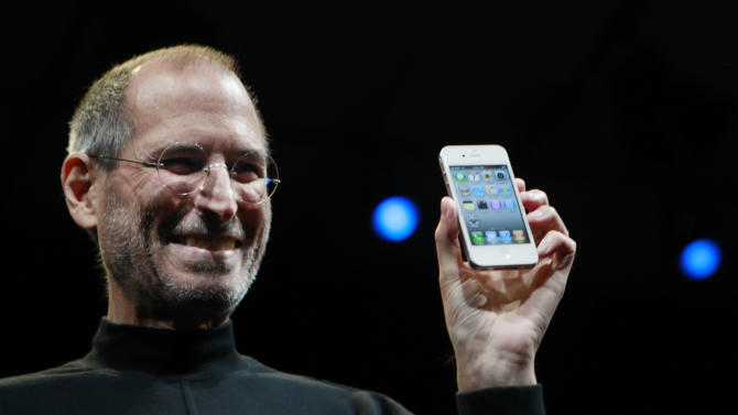 "FILE - In this June 7, 2010, file photo, Apple CEO Steve Jobs smiles with a new iPhone at the Apple Worldwide Developers Conference in San Francisco. In the white-hot competition for tech talent, some workers are alleging Silicon Valley's top companies conspired to keep employees from switching teams. A federal class-action suit claims that senior executives at Google, Intel, Adobe, Intuit, Lucasfilm, Pixar and Apple entered into secret anti-poaching agreements not to hire each other's best workers. And plaintiffs say e-mails uncovered during a U.S. Justice Department investigation put Steve Jobs at the center of the alleged conspiracy of so-called ""gentlemen's agreements."" The defendants say there was no conspiring, just one-to-one pacts between individual companies in the course of doing business and collaborating on innovative products. Apple is seeking to have the case thrown out. (AP Photo/Paul Sakuma, File)"