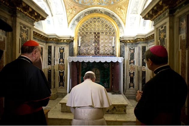 In this picture made available by the Vatican newspaper L'Osservatore Romano, Pope Francis, flanked by Cardinal Angelo Comastri, left, and Bishop Vittorio Lanzani, right, kneels in prayer in front of