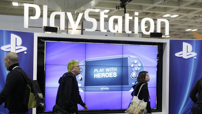 FILE- This March 8, 2012 file photo shows attendees walking past the Sony PlayStation PS Vita console on display in the Sony PlayStation booth at the Game Developers Conference in San Francisco.  Sony's PlayStation network remains offline on Frday, Dec. 26, 2014, in an outage that began as video game players unwrapped new consoles on Christmas. Microsoft's Xbox Live service, which had also gone down, is back online but the company says some applications aren't fully functioning. (AP Photo/Paul Sakuma, File)