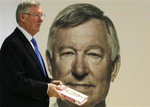 Former Manchester United manager Alex Ferguson poses with his new autobiography before a book signing at a supermarket in Manchester