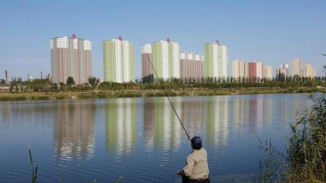 A resident fishes at a lake near apartment blocks in Beijing