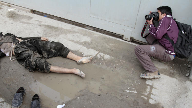 An Afghan photographer takes photos of an insurgent's body at the scene where he was shot to death near an Afghan intelligence office in Kabul, Afghanistan, Sunday, Feb. 24, 2013. A series of early morning attacks hit eastern Afghanistan Sunday, with three separate suicide bombings in outlying provinces and a shootout between security forces and a would-be attacker in the capital city of Kabul. (AP Photo/Musadeq Sadeq)