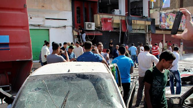 Libyan men inspect damaged vehicles at the scene of a car bomb explosion in Benghazi, Libya, Monday, May 13, 2013. A car bomb exploded Monday near a hospital in the eastern Libyan city of Benghazi, killing at least 10 people, officials said, in one of the biggest attacks since the end of the civil war that ousted former dictator Moammar Gadhafi. (AP Photo/Mahmoud Sohim)