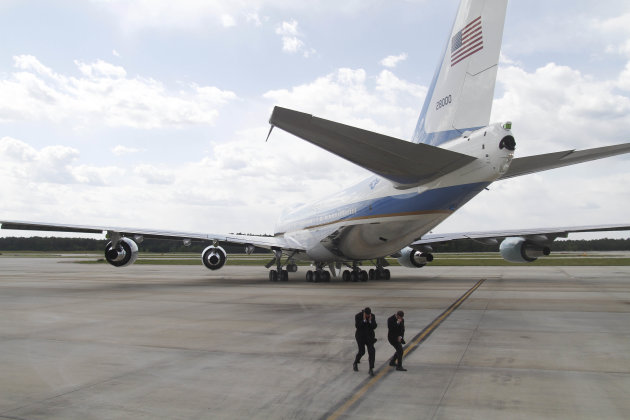 Secret Service Agents brace for the jet wash of Air Force One, with President Barack aboard, as it departs from Raleigh Durham International Airport in Morrisville, N.C., Tuesday, April 24, 2012. (AP