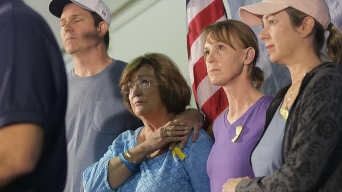 Family members of the victims of recent severe weather, from left, Mark Combs, Marry Ann Charba, Kim Charba and Cristen Daniel listen to an update during a news conference, Thursday, May 28, 2015, in Wimberley, Texas.  At least eight people are still missing in Hays County. (AP Photo/Eric Gay)