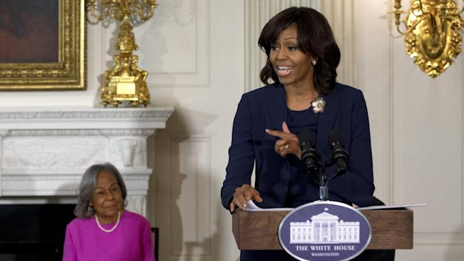 """First Lady Michelle Obama introduces a panel of the cast and crew of the movie """"42"""", next to Rachel Robinson, widow of baseball great Jackie Robinson, before a workshop for high school and college students, Tuesday, April 2, 2013, in the State Dining Room of the White House in Washington.  (AP Photo/Jacquelyn Martin)"""
