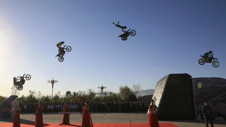 Riders perform stunt jumps on their motorcycles above musicians playing Chinese traditional instruments during the opening ceremony of a forum in Linfen