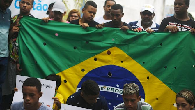 People protest before the burial of five youths killed after being shot by police officers in Costa Barros neighborhood, in Rio de Janeiro
