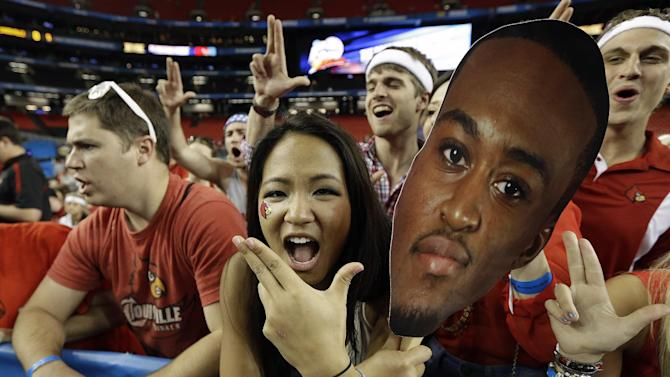 Louisville fans cheer and hold a photo of Louisville guard Kevin Ware before the first half of the NCAA Final Four tournament college basketball championship game between Michigan and Louisville, Monday, April 8, 2013, in Atlanta. (AP Photo/David J. Phillip)