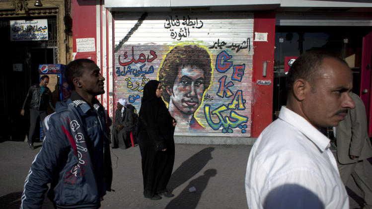 """Egyptians walk past a mural depicting a man who was killed during the revolution with Arabic that reads """"martyr Gaber, your blood will be the spark of the revolution,"""" at Tahrir Square in Cairo, Egypt, Thursday, Dec. 13, 2012. Egyptian President Mohammed Morsi's Muslim Brotherhood and other Islamists have been plastering posters across much of the country urging Egyptians to vote """"yes"""" and listing what they call the advantages of the new charter. """"Yes, to protecting (Islamic) Sharia (laws),"""" says a Brotherhood website. The Islamists have also been using mosques to disseminate the """"yes"""" message and putting to use their appeal to uneducated Egyptians in rural areas. But the pros and cons of the draft constitution and the question of whether it will be passed have grown more akin to being a secondary narrative to the worst crisis to hit Egypt since the overthrow nearly two years ago of Hosni Mubarak's authoritarian regime.(AP Photo/Nasser Nasser)"""