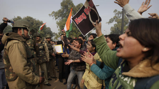 Protesters taunt police officers during a protest in New Delhi, Sunday, Dec. 23, 2012. Police in India's capital used tear gas and water cannons for a second day Sunday in a high-security zone to break up protests by thousands of people demonstrating against the gang rape and beating of a 23-year-old student on a bus. (AP Photo/Altaf Qadri)