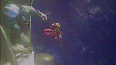 U.S. Coast Guard members retrieve a life preserver ring from the cargo ship El Faro in this still image from a U.S. Coast Guard handout video