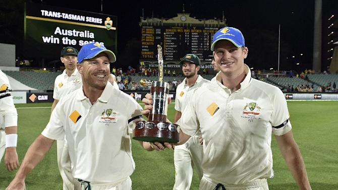 Australia's team captain Steve Smith (R) and teammate David Warner smile as they walk back with the Trans-Tasman trophy after defeating New Zealand in the first day-night cricket Test match at the Adelaide Oval on November 29, 2015