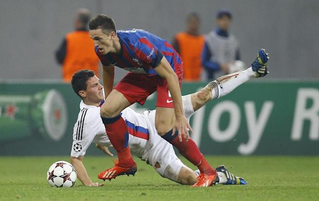 Basel's Fabian Schar, rear, and Bucharest's Florin Gardos struggle for the ball during the Champions League group E soccer match between Steaua Bucharest and FC Basel, in Bucharest, Romania, on Tuesda