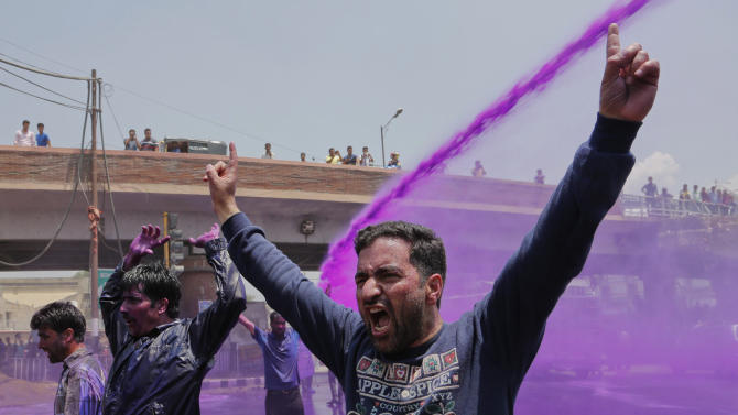 Colored water from water cannons hit Kashmiri government employees shouting slogans during a protest in Srinagar, India, Thursday, May 28, 2015. Police detained dozens of government employees who protested demanding regularization of contractual jobs and a hike in salary. (AP Photo/Mukhtar Khan)