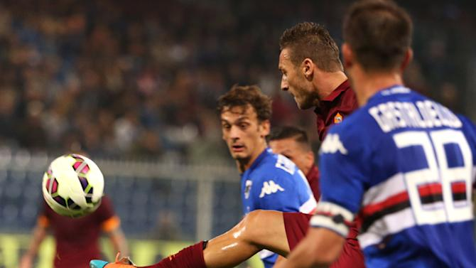 AS Roma forward Francesco Totti, center, controls the ball next to Sampdoria defender Daniele Gastaldello, foreground, and his teammate Manolo Gabbiadini during a Serie A soccer match between Sampdoria and AS Roma, in Genoa, Italy, Saturday, Oct 25, 2014. (AP Photo/Carlo Baroncini)