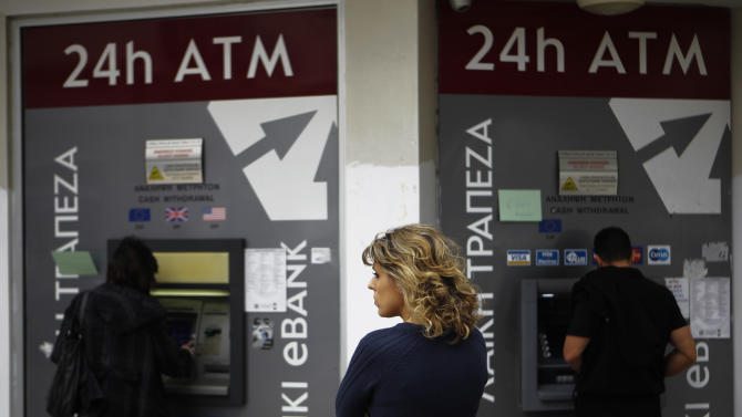 A woman waits as  two people use the ATM machines in central capital Nicosia, Cyprus, Friday, March 22, 2013. Cypriot authorities were putting the final touches Friday to a plan they hope will convince international lenders to provide the money the country urgently needs to avoid bankruptcy within days. (AP Photo/Petros Karadjias)