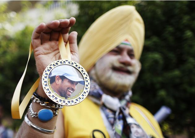 A cricket fan holds a medal with a portait of cricketer Sachin Tendulkar while posing for photographers outside a stadium in Mumbai