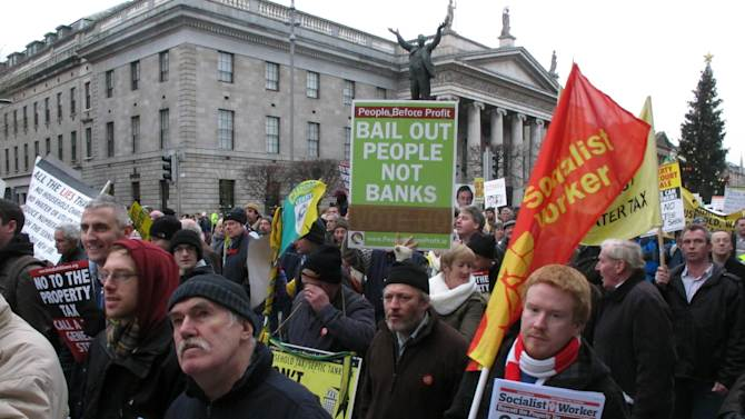 Socialist protesters march past Dublin's General Post Office in opposition to imminent spending cuts Saturday, Nov. 24, 2012. The government says it will unveil Ireland's sixth straight austerity budget next month in hopes of reducing the country's 2013 deficit to 8.6 percent, still nearly triple the spending limit that eurozone members are supposed to observe. (AP Photo/Shawn Pogatchnik)